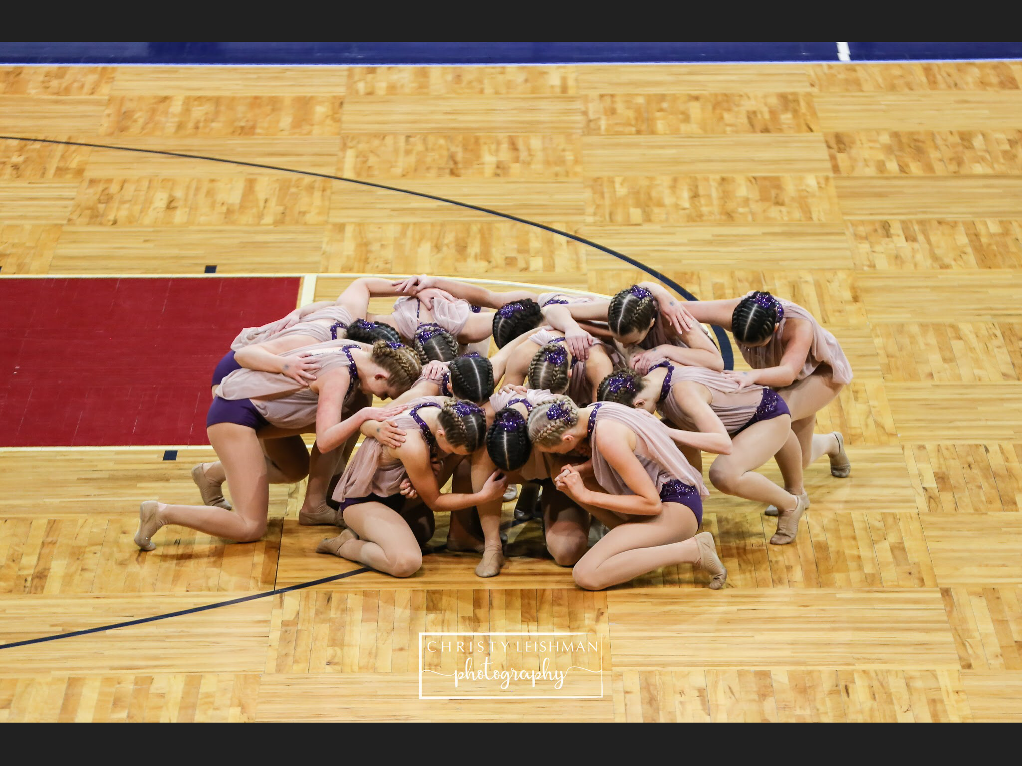 Photo By: Christy Leishman  As the team finishes their State performance, the girls end in a huddle on the floor, showing their emotion.