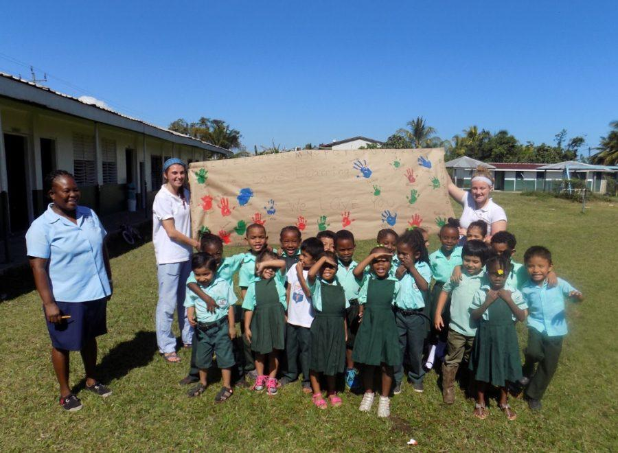 Anselmi (top right holding poster) surrounded by the class of 4-5 year olds she helped with, led by teacher Mrs. Arru (Far left) at St. Peter Claver school in Belize. Photo By: Isabella Song '19
