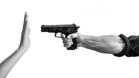 A gun pointed towards a hand.