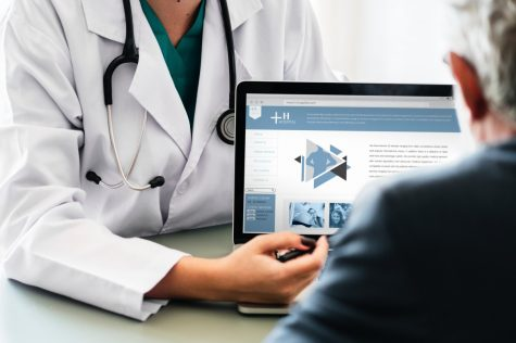 A doctor talking to a patient showing them a laptop